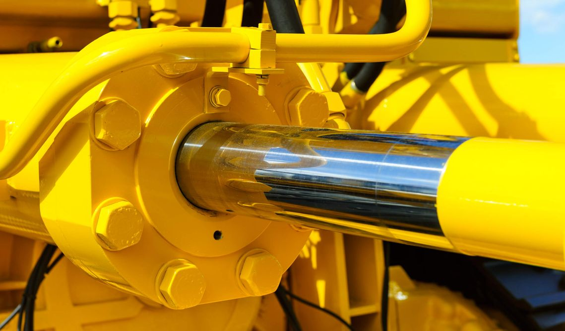yellow machine with large hydraulic cylinder